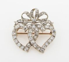 A Victorian double heart brooch, the entwined hearts each set with cushion shaped diamonds and surmounted with a diamond set bow, in silver and gold. 3cm wide.
