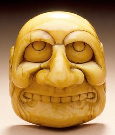Netsuke in the shape of a Buaku mask. 18th-19th century, Japan. Ivory with staining, sumi e. LACMA ( Raymond and Frances Bushell Collection)