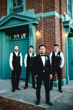 Handsome groom wears black three piece suit with bow tie with groomsmen in vests