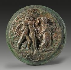 Lid of a Etruscan bronze mirror with a relief depicting the drunken Dionysos leaning on the young Eros. Both are accompanied by a maenad dressed in long, waving clothes and playing the kithara. 3rd century B.C.