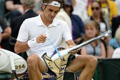 Roger Federer works on his racket during a changeover
