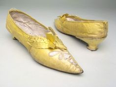 Manchester City Galleries item 1951.436,  1790-1800, Yellow kid over white kid and linen, bound with yellow silk ribbon. Sharply pointed toe. Cut out pattern, outlined in chain stitch and showing white satin on front. Pleated band of yellow silk ribbon with central rosette, round front instep. Heel broad under instep, narrowing to small waist and base. Kid worn and torn on heels.