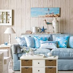 Seaside living room with white-washed wall panelling, a light blue sofa piled with cushions and an armchair, a coffee table chest and side table with lamp. Beach Cottage Style, Beach Cottage Decor, Coastal Style, Coastal Cottage, Coastal Decor, Seaside Decor, Nautical Style, Seaside Style, Modern Coastal