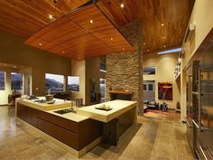 Modern Zen Kitchen Design - This alluring contemporary kitchen infuses Zen style, such as a neutral color scheme, wooden ceilings, and a stone fireplace.