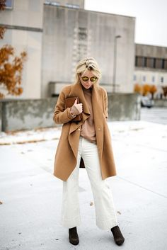 Blogger Happily Grey looks elevated in a camel coat, neutral top, white jeans, brown suede boots, mirrored sunglasses, and a clutch