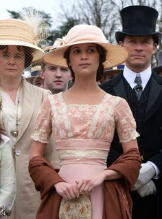 Testament of Youth (2015) - Alicia Vikander as Vera Brittain wearing a short-sleeved pale pink satin dress with white lace embellishments on the bodice. The accessories include a hat a burnt brown shawl and an embroidered chain bag.  The costumes were designed by Consolata Boyle.