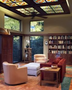 A comfortable living room/library combination receives distinction for large transom windows and a dropped ceiling with lighted, stained glass panels  (via Harrell Remodeling)
