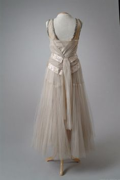 Date Made 1923 Designer Callot Soeurs 1923 Description White silk net party dress accented with watered silk satin ribbon rosette. The under-skirt is edged with lace and the shoulder straps are edged in rhinestones. Fine example of early 1920's high style. Back