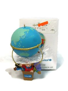 "2010 Hallmark Keepsake Christmas Ornament  A World of Joy Unicef with Original Box  Measurements: The globe ballon is 7"" round and the Overall Length of the ornament is 4""  Lovely ornament features the word ""joy"" in the six official United Nations languages----English, Spanish, French, Arabic, Chinese and Russian. Handcrafted and Designed by Artist Sue Tague. Dated 2010. A sensational addition to your collection."
