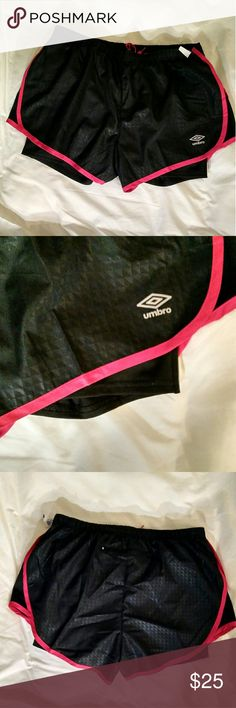 Umbro Jogging Soccer Shorts Nice women's shorts with built in bike shorts. They have an elastic/ drawstring waist and a ziipperrd inside back pocket. Black squared/diamond imprint with hot pink strip. Umbro Shorts