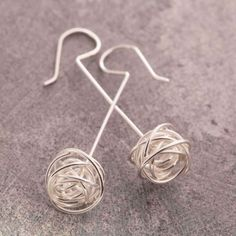Nest Silver Drop Earrings - In these Nest Silver Drop Earrings fine silver wire is wrapped in a seemingly haphazard fashion into a delicate silver nest, before being placed onto a long silver stem creating these elegant and contemporary drop earrings. #Otisjaxon #Jewellery