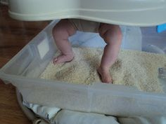 Baby sensory play. Put a tub full of sand/water under a jumparoo for baby to feel and learn!