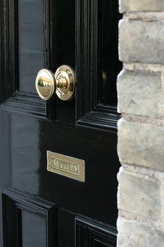 Golden doorknobs and letterbox on black door #doorknobs #letterboxes