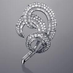 A Mid-20th Century platinum brooch with diamonds in a stylized double feather motif by Cartier. This brooch features 132 round-cut diamonds with an approximate total weight of 5.00 carats, and 48 baguette diamonds with an approximate total weight of 4.00 carats, VS clarity and G-H-I color grade. With signed Cartier Box. Circa: 1952