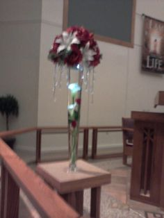 Alter arrangement.Tall pilsner vase with 2 real touch calla lillies and two red roses submerged in water and a large ball type arrangement atop it with cascading gems dangle off the sides for drama a submercable water lite from the bottom of the top arrangment to glow onto the flowers