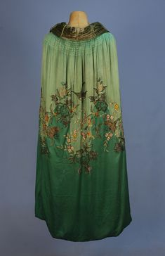 Back / BEADED and EMBROIDERED SILK EVENING CAPE, 1920's. Two shades of green satin embroidered in pastel silk and chenille, with gold metallic threads, having bronze seed and crystal bugle beads and sequins in an undulating pattern of swallows, flowers and butterflies, with panne velvet lining and ruched collar.