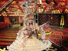 Kazakh girl in her traditional regalia playing the 'Dombra' in her Yurt (dwelling), Kazakhstan, Central Asia