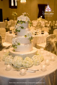 White wedding cake with white sugar flowers and pearls.