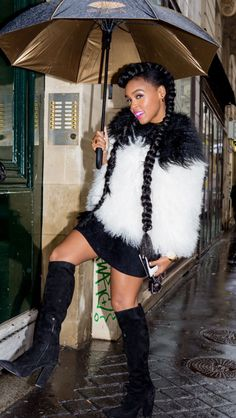 Janelle Monae rocking a black and white feathered coat, black mini skirt and knee-high boots