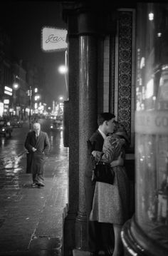A rainy night in Oxford Street where a young couple seek a tender moment in a doorway. © Philip Jones Griffiths / Magnum Photos