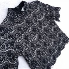 Nasty Gal lace scallop hem high neck crop tee Gorgeous lace top from JOA (Nasty Gal brand). Beautiful black floral lace design with nude cream underneath. High neckline but not turtle neck high. Cute scallop hem detail around the bottom and sleeves. Short tee style sleeve. Cropped but not so short that it shows anything (I'm 5'7 and it covers my stomach). It is oversized so for a more fitted look it would be best on a medium (as long as you aren't SUPER busty). Perfect for spring and summer…