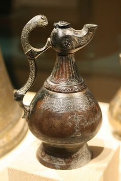Ewer with Lamp-shaped Spout late 12th century Iran, Khurasan Brass; cast, chased, engraved, inlaid with silver and black compoundwishes to the owner.