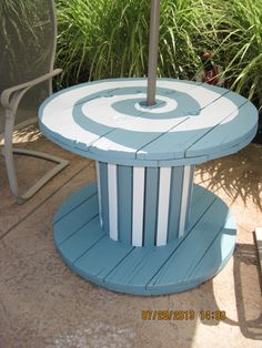 Painted an old wooden spool and, with a patio umbrella we found on clearance, made a cute outdoor table for by the pool!