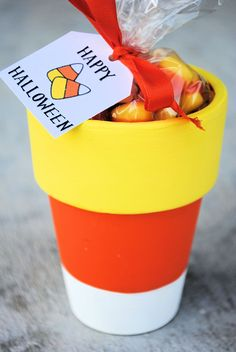 Paint a Tall Flower Pot like a Candy Corn {and free printable}...they have this tall-style pot at Michaels...cute party favor or teacher gift