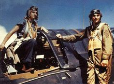 A pilot and his more casually dressed gunner pose with their late model SB2C Helldiver dive bomber sometime after October 1944.