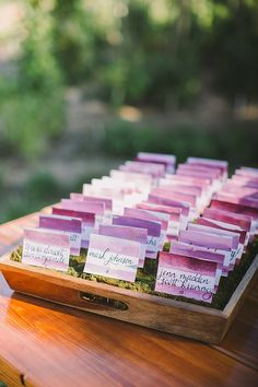 Purple watercolor wedding escort cards nestled on moss for garden wedding #escortcards #wedding #weddingideas #stationery #watercolor #gardenwedding #purplewedding
