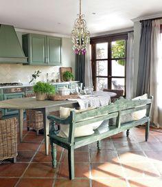 Cocina con suelo de barro cocido, mobiliario en verde y lámpara de araña