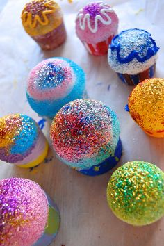 How fun would these be to make!  pretend cupcakes from polystyrene balls, egg crates, glitter glue, & puffy paint