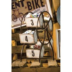 Tabletop storage gets a fusion of industrial and whimsical style with this Ferris wheel. As the Ferris wheel really turns you can access the 5 numbered metal storage bins. Each bin is coated with a book page design and a large black number.
