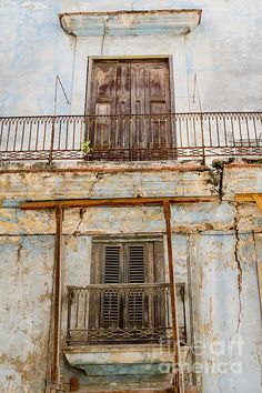 Temporary, Havana Cuba. A heavy concrete balcony supported by tentative timbers on a street in Havana, Cuba. One imagines this is only a temporary arrangement and the weight of the balcony will overcome.  Fine Art Photography http://rob-huntley.artistwebsites.com © Rob Huntley