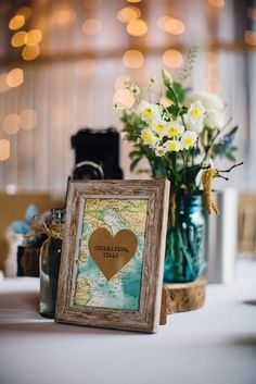 Vintage map Table Place Names with blue bottles filled with flowers on a wooden slab as table centre pieces | Travel Theme Decor | Vintage Maps | Rustic Barn Reception | Spring Wedding | Image by Samuel Docker Photography | http://www.rockmywedding.co.uk/lorna-george/