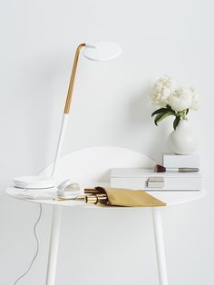 Pixo LED Table Lamp in White and Brass. Available in eight playful colors, Pixo is infinitely adjustable and has a built-in USB port for charging your phone.