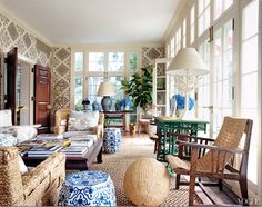 Tory Burch's solarium is all kinds of wonderful.  Great textured rug and vintage John Himmel chairs.  The fabric on the walls and chairs are both from Quadrille.  The walls just make the room.   Love the blue and white garden seats.  The doors are so beautiful too.