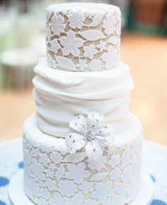 Lace wedding cake - Dark-ivory fondant with an off-white fondant lace covering decorated the top and bottom tiers, while a fondant swag wrapped the middle one. A silver sugar flower completed the look.