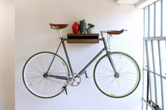 I will need to do this in my next place ~ a lot of us have our bike hanging somewhere but to also use it for a shelf just makes it cool!