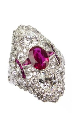 Early 20th century three stone Burma ruby and diamond 'vertical' cluster ring, c.1905, centred by a oval cut Burma ruby with pear shaped diamond above and below, framed by a pierced diamond cluster scroll border of curved lozenge outline, with calibre cut ruby and diamond collet accents, millegrain set, accompanied by AGL report no. CS71044 giving the Burma origin opinion for the principal ruby and that the stone shows no evidence of heat treatment.  At SJ Phillips.