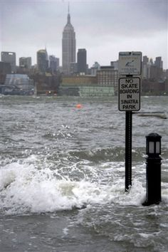 NYC. The Hudson River swells and rises over the banks of the Hoboken, N.J. waterfront as Hurricane Sandyapproaches on Monday, Oct. 29, 2012. Hurricane Sandy continued on its path Monday, forcing the shutdown of mass transit, schools and financial markets, sending coastal residents fleeing, and threatening a dangerous mix of high winds and soaking rain. (AP Photo/Charles Sykes) (AP Photo/Charles Sykes)
