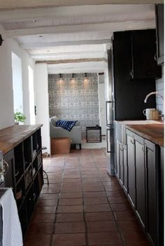 Dark contrasts with gleaming white and intricate tiles in this rustic modern kitchen. Minimal with a nod to traditional Shaker style. Dark Kitchen Cabinets, Black Cabinets, Kitchen Tiles, Minimal Kitchen Design, Hacienda Homes, Terracotta Floor, Beach House Kitchens, Flat Interior, Modern Rustic Interiors