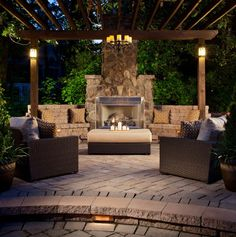 Moody lighting, comfy wicker furniture, a vine-wrapped pergola and a custom fireplace make this the most popular outdoor entertaining space....