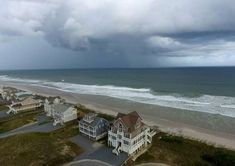 a sandy beach next to a body of water: A storm front passes homes in North Topsail Beach, N., prior to Hurricane Florence moving toward the east coast on Wednesday, Sept. North Topsail Beach, Storm Front, Winter Storm, Dancing In The Rain, Natural Disasters, East Coast, Mother Nature, Amazing Photography, Florence