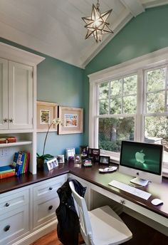 teal wall color + wooden countertop + white cabinets