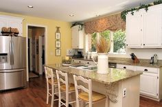 Cheery yellow walls in this granite and stainless steel #kitchen.