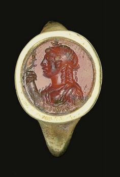 A ROMAN GOLD AND CARNELIAN FINGER RING   CIRCA 1ST CENTURY B.C.-1ST CENTURY A.D.   The plain hoop flat on the interior, rounded on the exterior, expanding to the broad shoulders, the high oval bezel with a flanged border, set with a flat oval stone engraved with a bust of Isis in profile to the left, wearing a diminutive Egyptian crown, her coiffure arranged in plaits falling to her shoulders, holding a staff in her raised right hand  7/8 in. (2.2 cm.) long