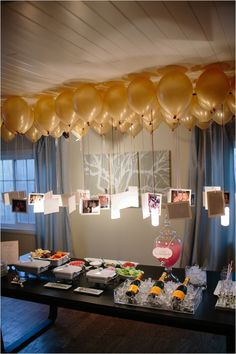 Photos hanging from balloons create a chandelier over a table.
