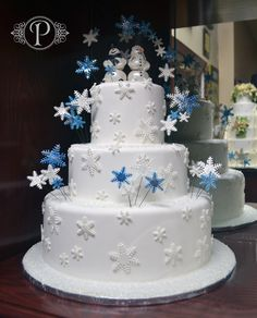 """A simple 3-tier cake with fondant snowflakes all around the sides of the tiers and in white and sparkly blue, coming out of the cake as well. To """"top"""" it off, a snowgroom and snowbride, made out of fondant stands on top of the top tier. This cake is beautiful and simple."""