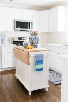 Crisp white cabinets and countertops pop against a rich wood floor. See Lemon Stripes' kitchen reveal for all the details.